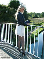 Gorgeous blonde Erin is outdoors showing off her shiny legs covered in silky nylon and her beautiful black stilettos